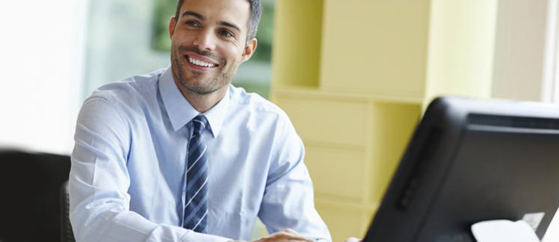 Male ABCO Technology student in a blue shirt with a blue striped tie learning in a cisco certified network associate program while smiling in-front of a computer