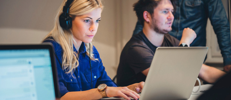 Female ABCO Technology student in blue shirt sitting infront of a laptop with headphones on learning how to become a website designer and developer