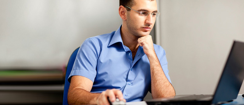 Male student in blue shirt sitting in a class staring intensely at a computer and studying for his 7 Month Oracle Database Administrator Career Training Program